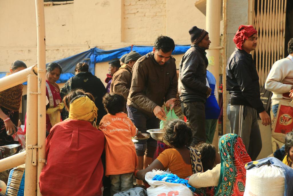 Die Bettler sitzen aufgereiht da und warten ab bis es Reis in die Reisschalen rieselt
